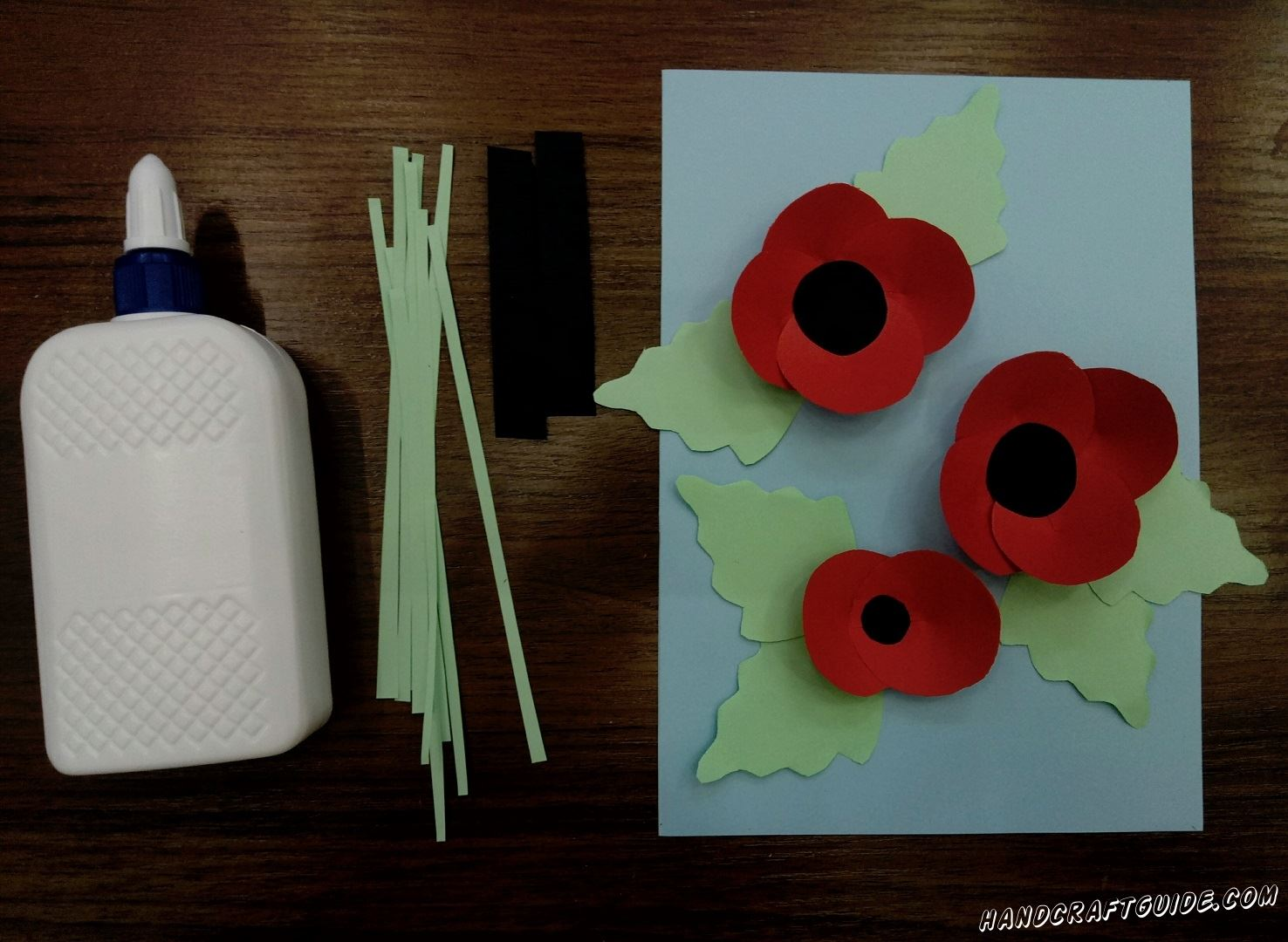 Далее, нам нужно взять наши чёрные кружки и вклеить их в каждый цветочек. Также под каждым нашим цветком нужно вклеить листочки