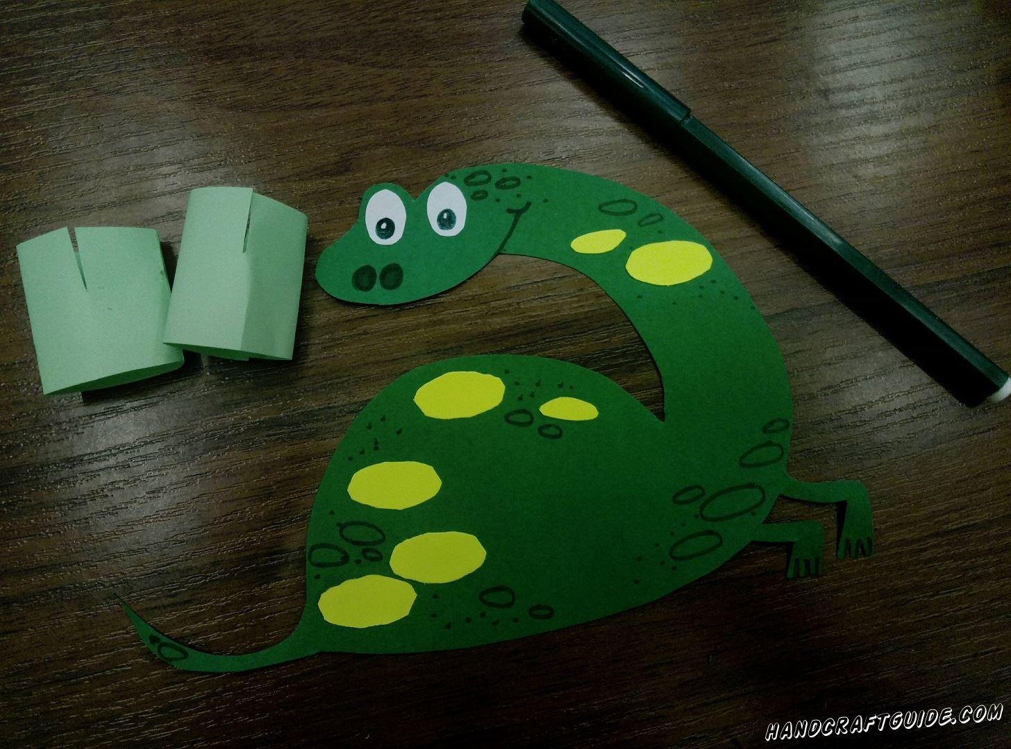 Но перед тем как вставить на подставочки нашего динозавра,его нужно красиво разрисовать, дорисовывая улыбочку , носик и пятнышки
