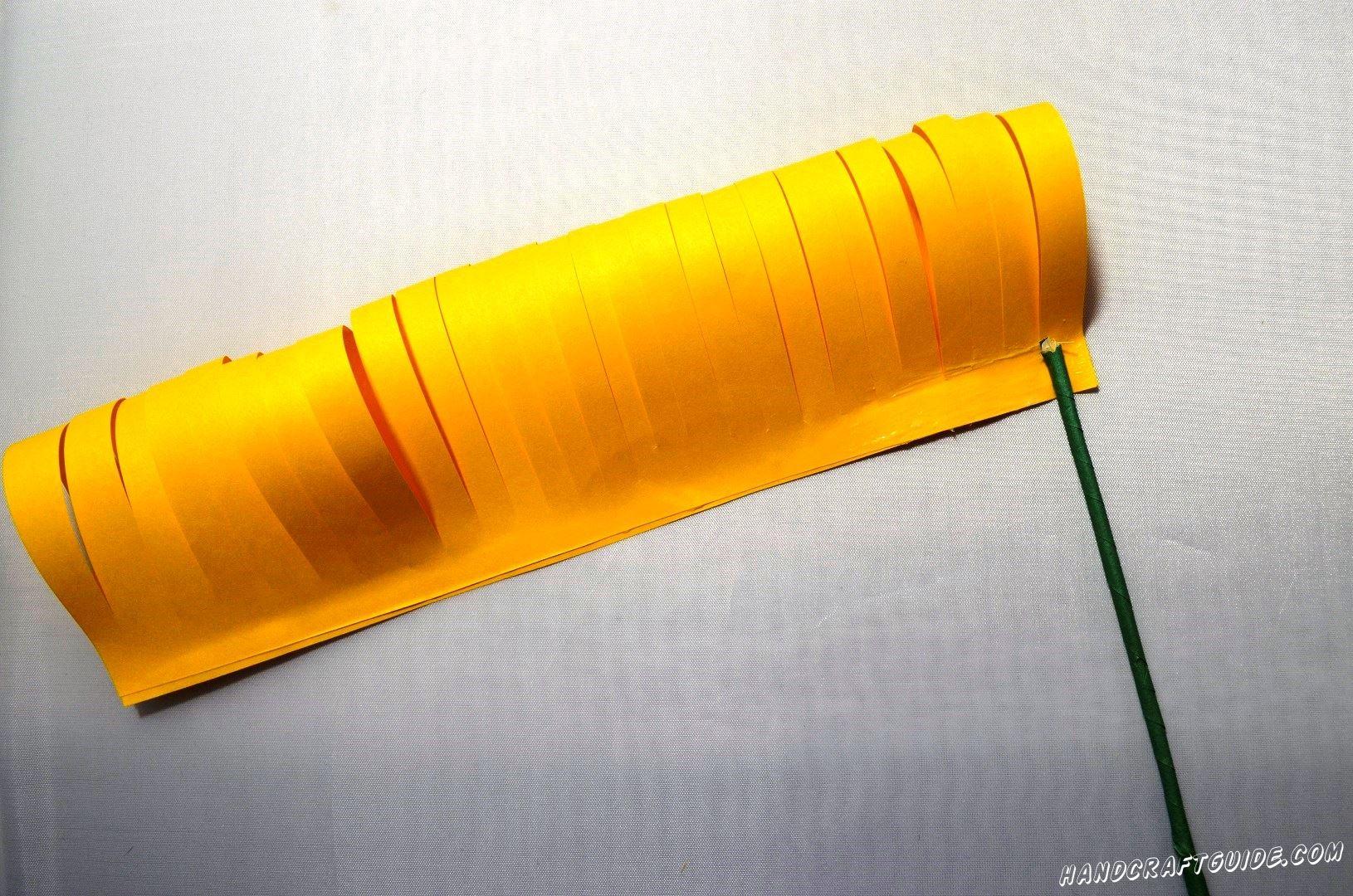 Склеенную полосочку начинаем наклеивать на трубочку из зелёной бумаги, которая будет стебельком.