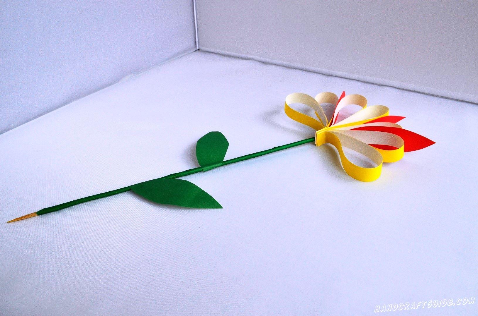 Приклеиваем желтый цветочек на шпажку, а между лепестками приклеиваем красные лепесточки