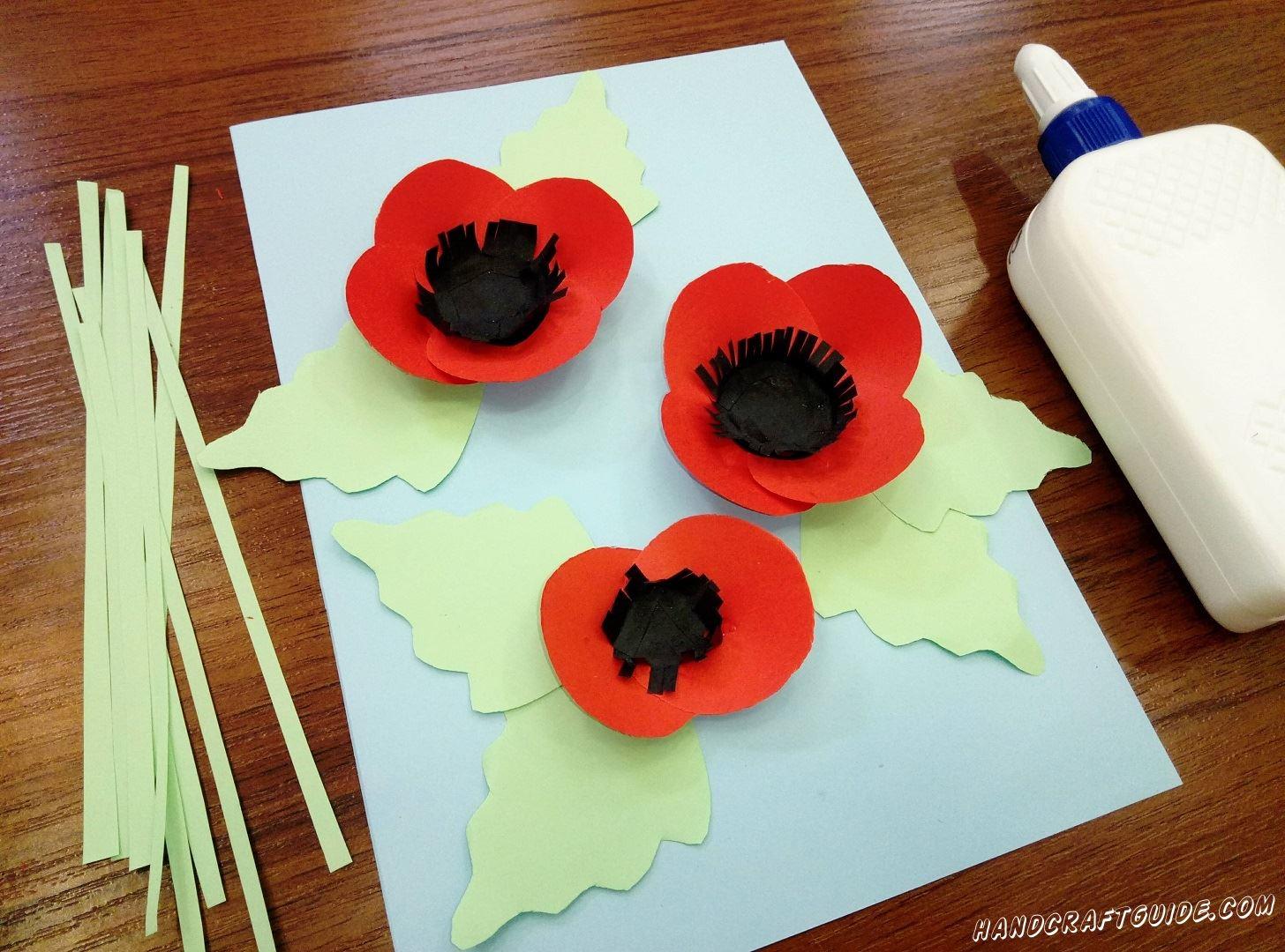После этого берём наши чёрные полосочки и ,склеивая концы, делаем из них кружки, которые мы наклеим на чёрную серединку в цветочках