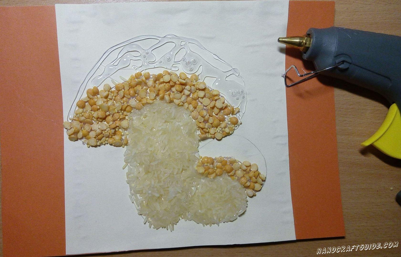 Затем обрабатываем клеем нижнюю часть шляпки грибов. Засыпаем эту часть горохом