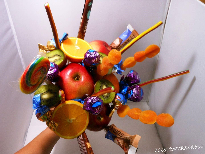 Теперь мы вставляем между фруктов шпажки с конфетами, батончиками, курагой, жвачками и другими любимыми сладостями.