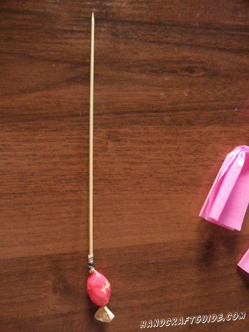 На конец шпажки приматываем конфетку, с помощью нитки