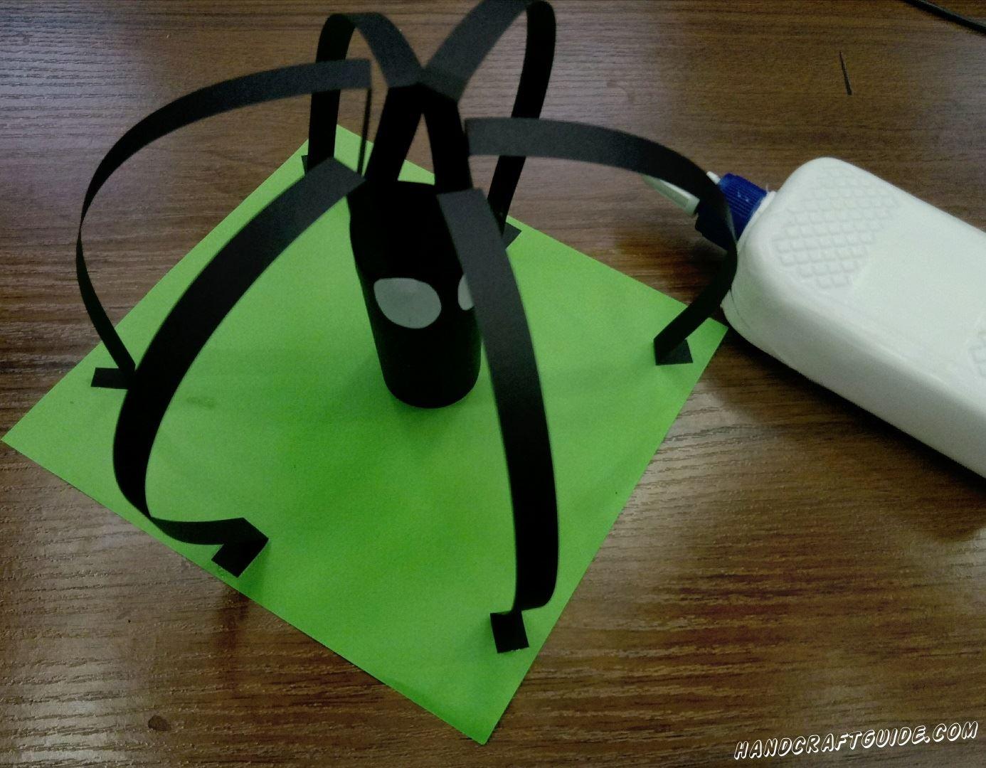 С помощью клея, прикрепляем лапки к зелёному листку бумаги