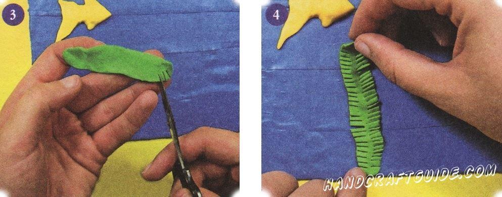 Скрутите зеленую колбаску и сделайте ее плоской. Вдоль краев сделайте несколько надрезов, оставляя полосу в центре нетронутой. Прикрепите полученную полоску вертикально на синем фоне. Теперь у вас есть морская водоросль.