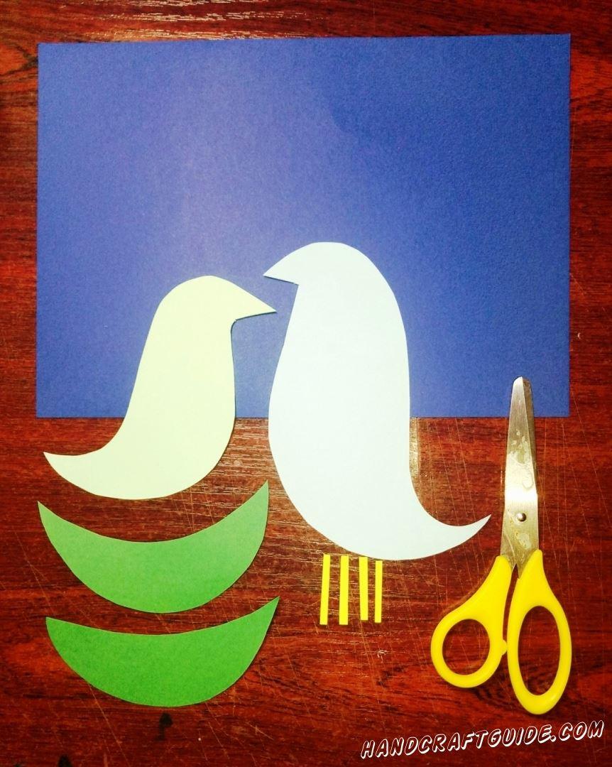 Из цветной бумаги мы вырезаем все необходимые фигурки: светло-голубую и светло-зелёную голубки, только голубая должна быть в два раза больше, четыре маленькие желтые полоски и два крылышка зелёного цвета