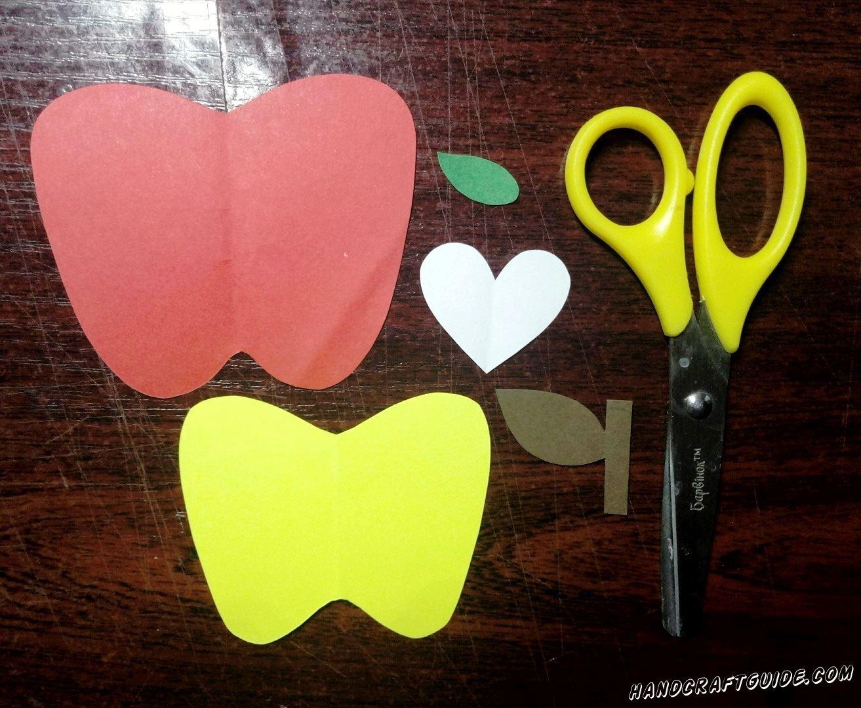 Давайте вырежем из бумаги красного цвета большое яблочко, к нему чуть меньшее яблоко желтого цвета, белое сердечко, веточка с листочком коричневого цвета и ещё зелёный листик.