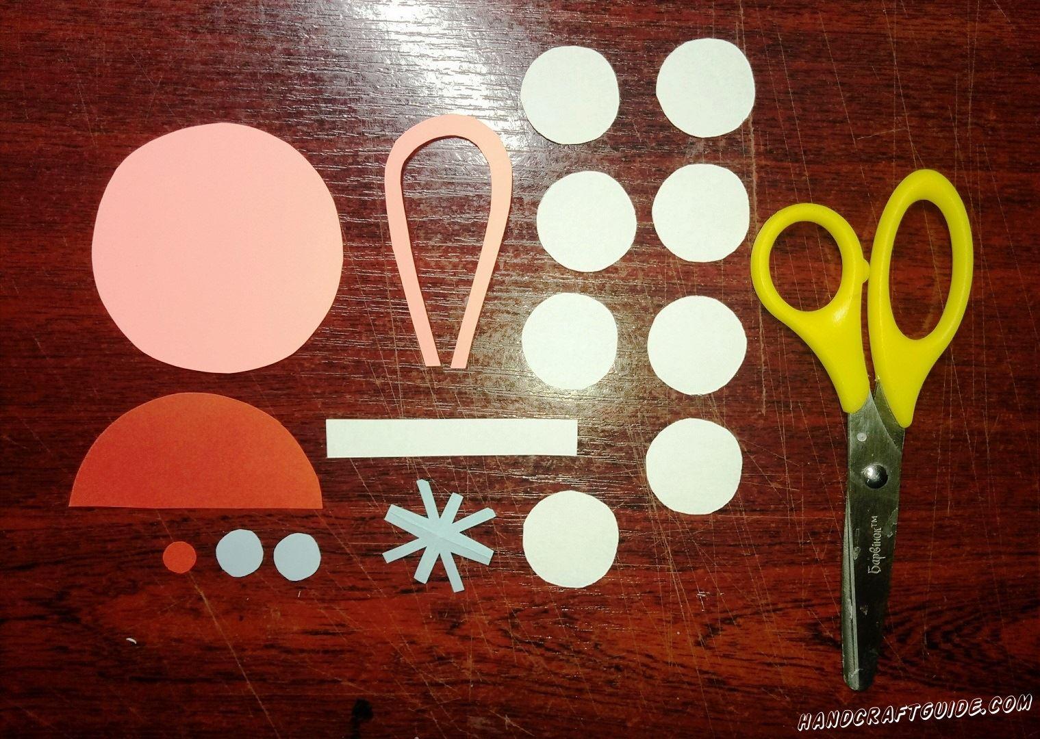 Берем в руки бумагу, ножницы и вырезаем восемь одинаковых белых кружочков. Также нам нужно вырезать белую полоску, голубую звёздочку и два кружочка, большой полукруг и маленький кружочек белого цвета. Также нам нужен большой розовый круг и петелька
