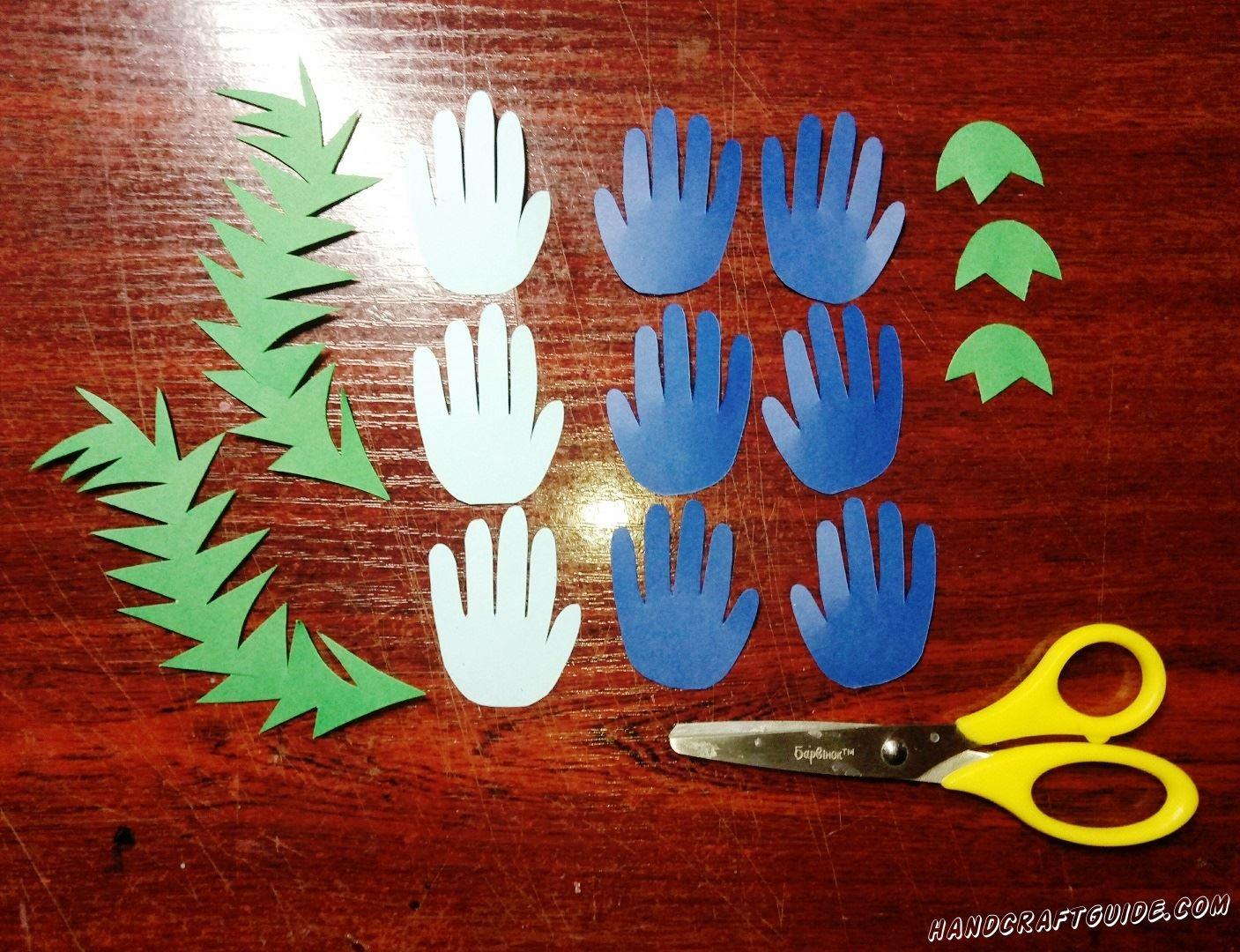 Для начала, нам нужно вырезать семь фигурок в форме ладошек синего цвета, и три «ладошки» из белой бумаги. Также нам понадобится две волнистые колючие травинки и три кувшинки зелёного цвета.