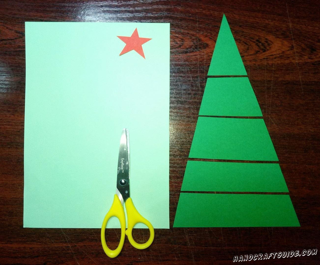 Из бумаги зелёного цвета мы вырезаем большой треугольник и разрезаем его на 5 частей, как показано на фото. Теперь вырезаем красную звёздочку