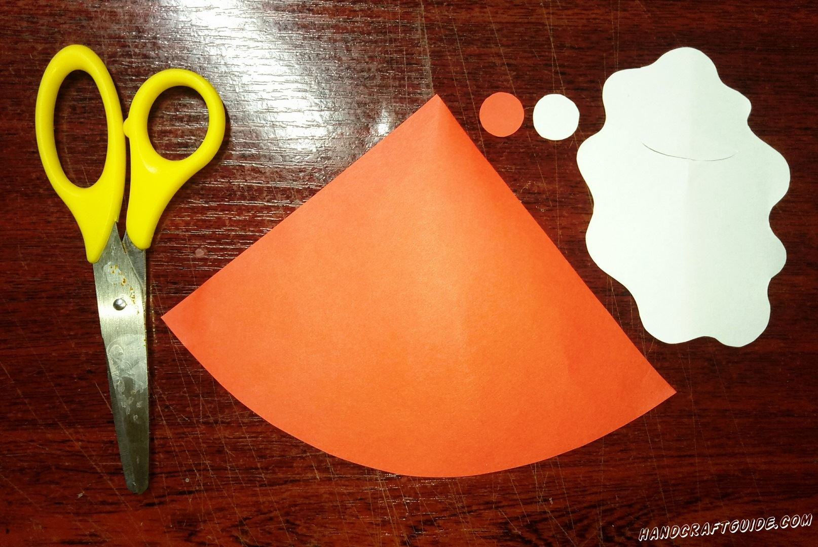 Для начала, нам нужно вырезать треугольник с закругленной длинной стороной и маленький кружочек красного цвета. Теперь берем белую бумагу и вырезаем фигурку, напоминающую лужицу, круг с волнистым ободком, и маленький кружочек.