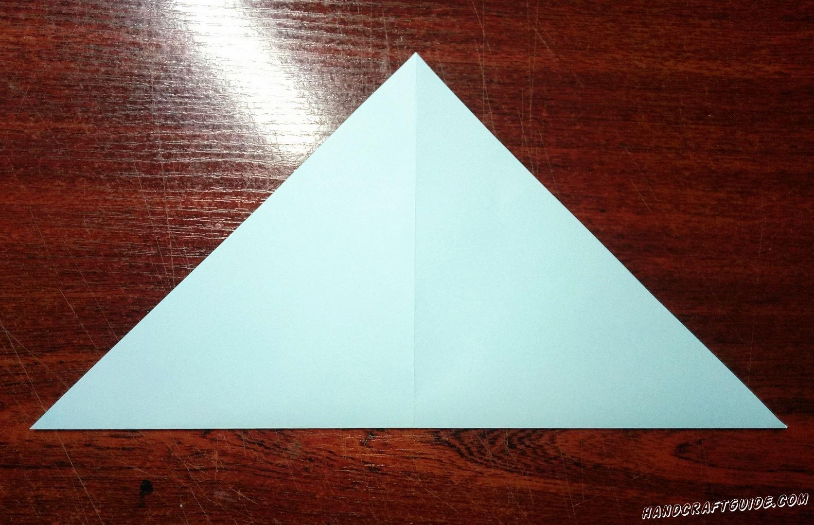 Берем квадратный, светло-голубой листочек бумаги и складываем его пополам в треугольник