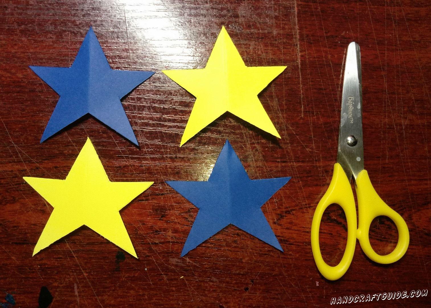 Вырезаем из бумаги четыре одинаковые звёздочки – две синие и две жёлтые