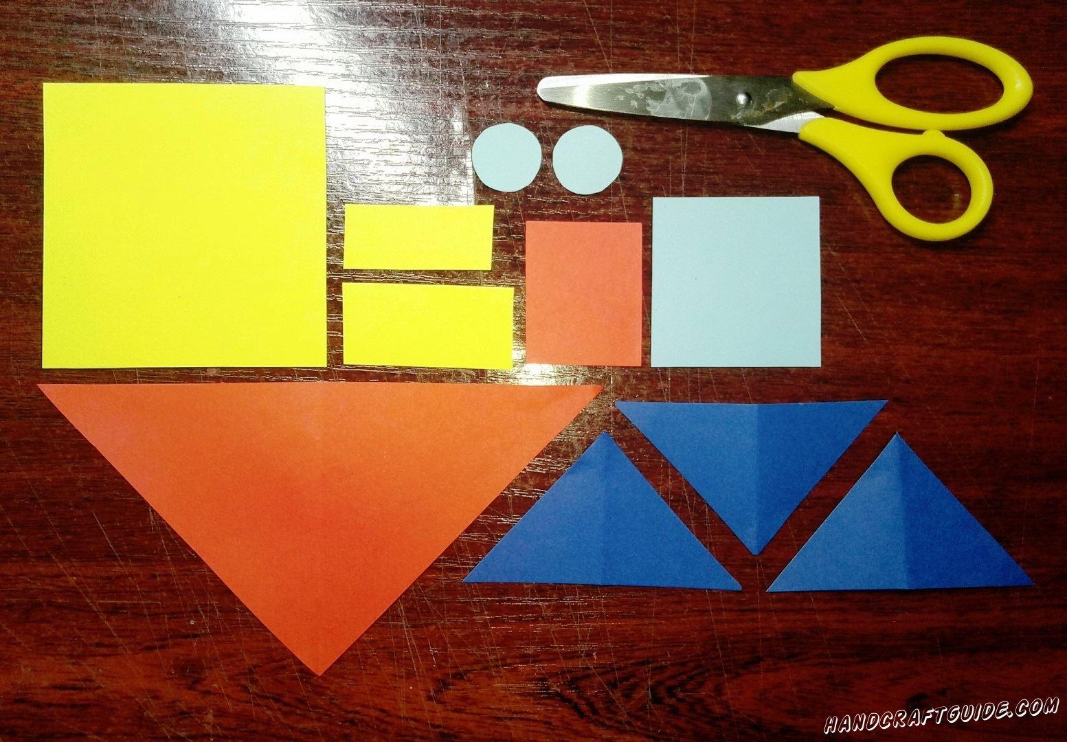Для начала берем в руки бумаги, ножницы и вырезаем все необходимые нам фигурки: квадрат и два прямоугольника желтого цвета, три треугольника синего цвета, красный большой треугольник и небольшой квадрат, квадрат и два кружочка голубого цвета.