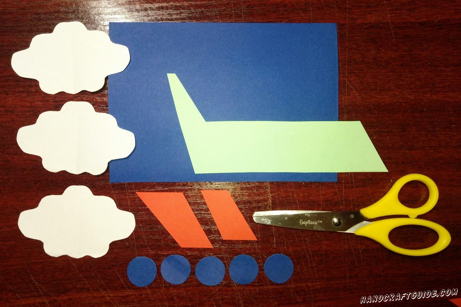 Из бумаги белого цвета мы вырезаем три облака. Теперь берем в руки цветную бумагу и вырезаем необходимые нам фигурки: светло-зелёный корпус самолёта, пять синих окошек и два красных крыла