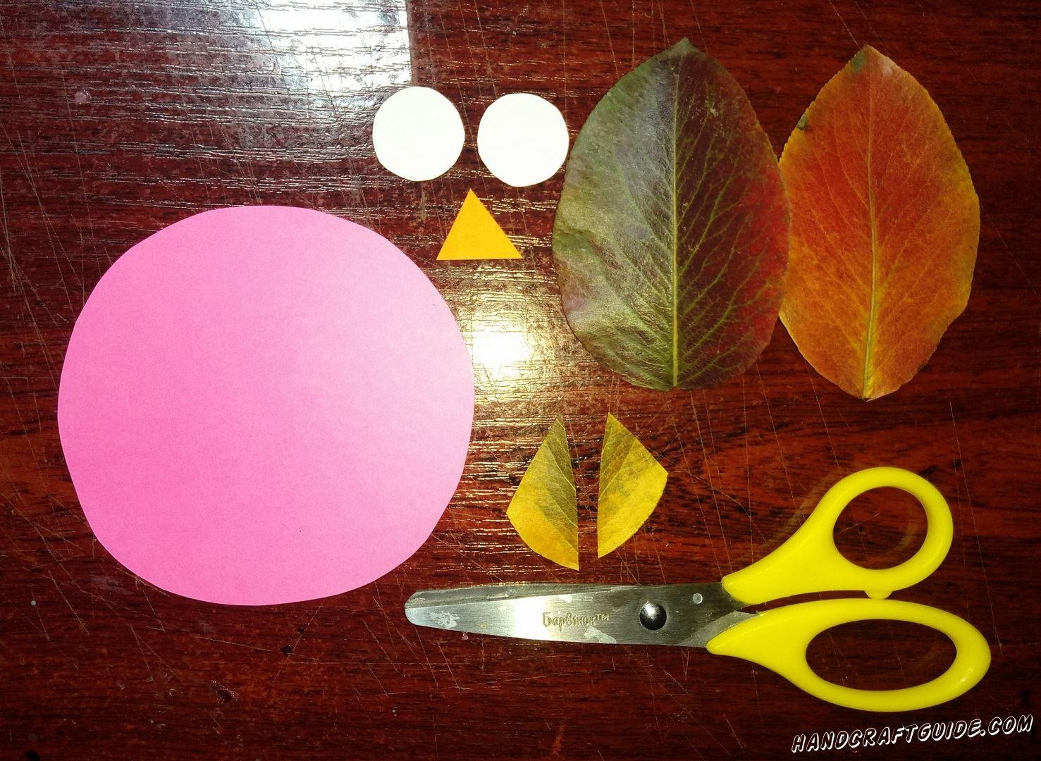 Давайте подготовим все необходимые нам фигурки: большой розовый круг из бумаги, два белых и один треугольник из бумаги желтого цвета. Также вырезаем два ушка из листочка с дерева