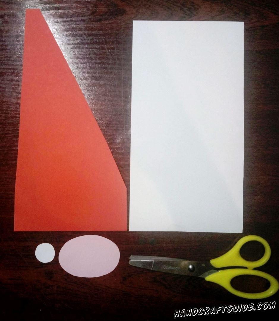 Для начала, нам нужно вырезать большой прямоугольный лист белого цвета, также белую полосочку и кружочек. Нам понадобится ещё овал розового цвета и красная шапочка в виде пятиугольника, как показано на фото