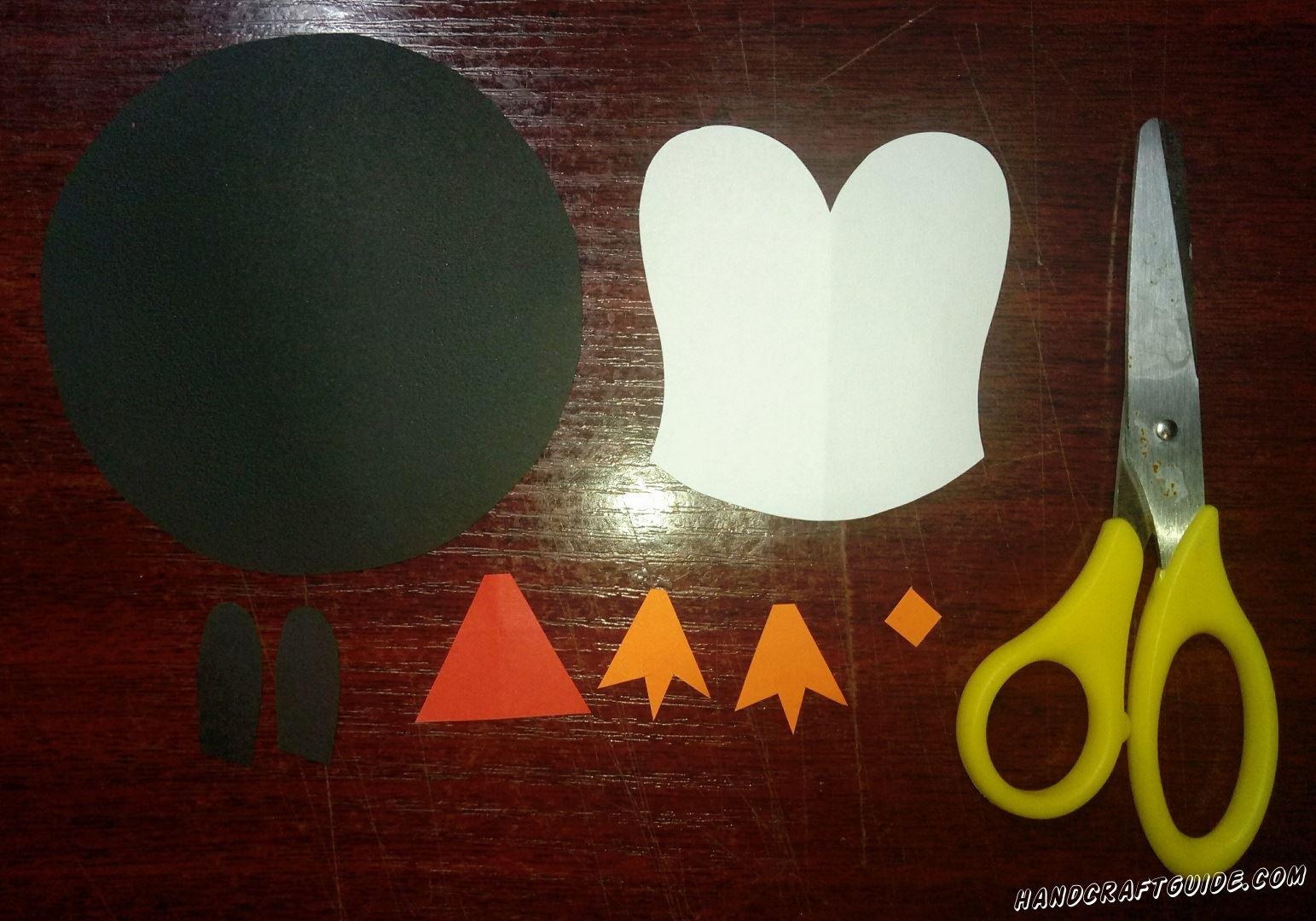 Для начала, нам нужно вырезать все необходимые бумажные фигурки: большой чёрный круг и два крылышка, белую грудку и мех для шапочки, красную шапочку, а также две лапки и клювик из бумаги оранжевого цвета