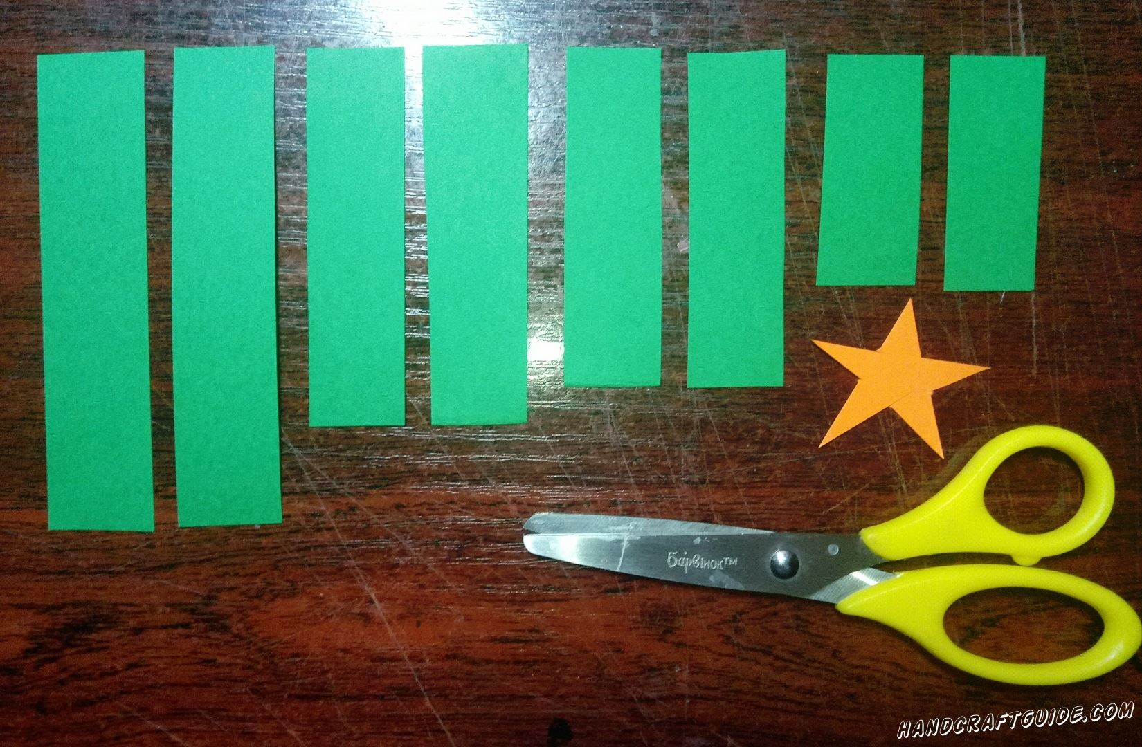 Вырезаем восемь полосок из бумаги зелёного цвета: две длинные, две чуть короче, потом ещё чуть короче, ну и последние две штучки будут самыми короткими. Также вырезаем оранжевую звёздочку.
