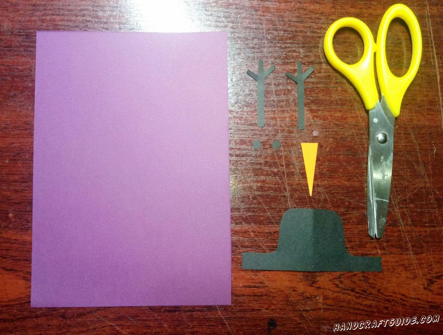 Из бумаги чёрного цвета  мы вырезаем две веточки-ручки, два глазика и шляпу. Также нам нужно вырезать оранжевый носик