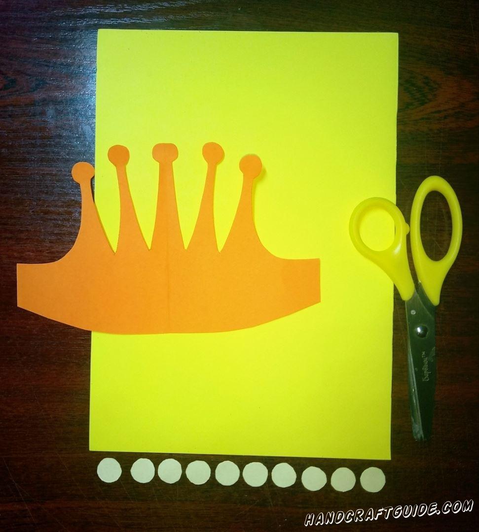 Вырезаем бумажную корону оранжевого цвета, а также десять маленьких светло-голубых кружочков. Важно использовать плотную бумагу в этой поделке.