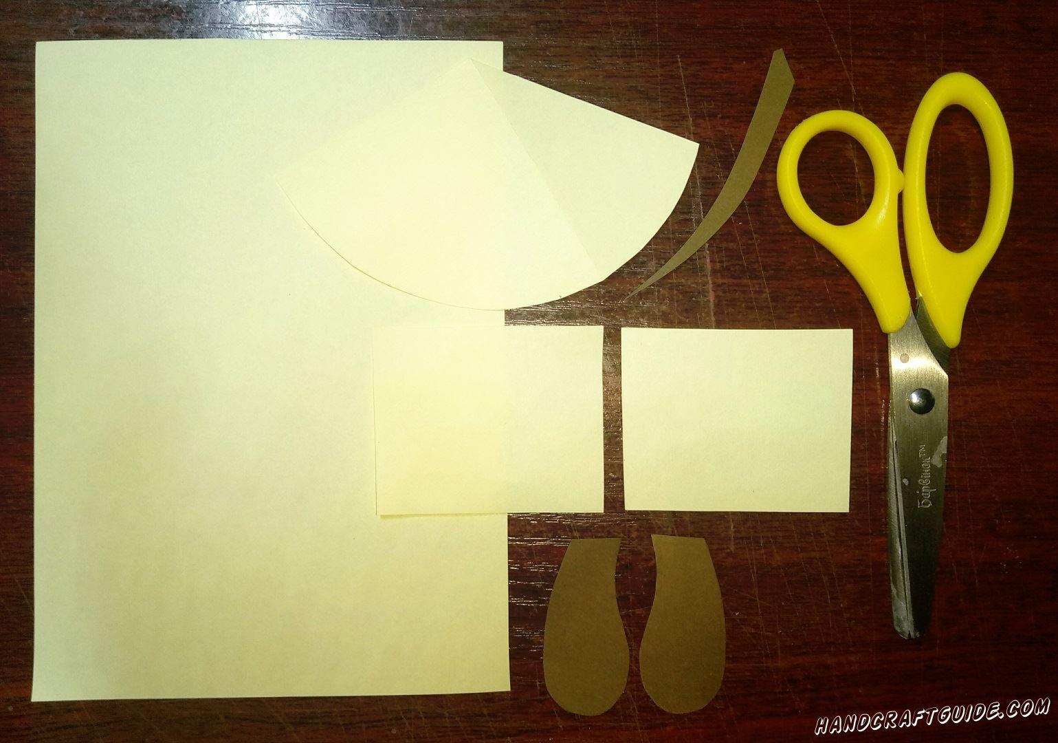 Из бумаги светло-жёлтого цвета мы вырезаем два одинаковых прямоугольника и треугольник с закругленной широкой стороной. Теперь берем коричневую бумагу и вырезаем два ушка и хвостик.