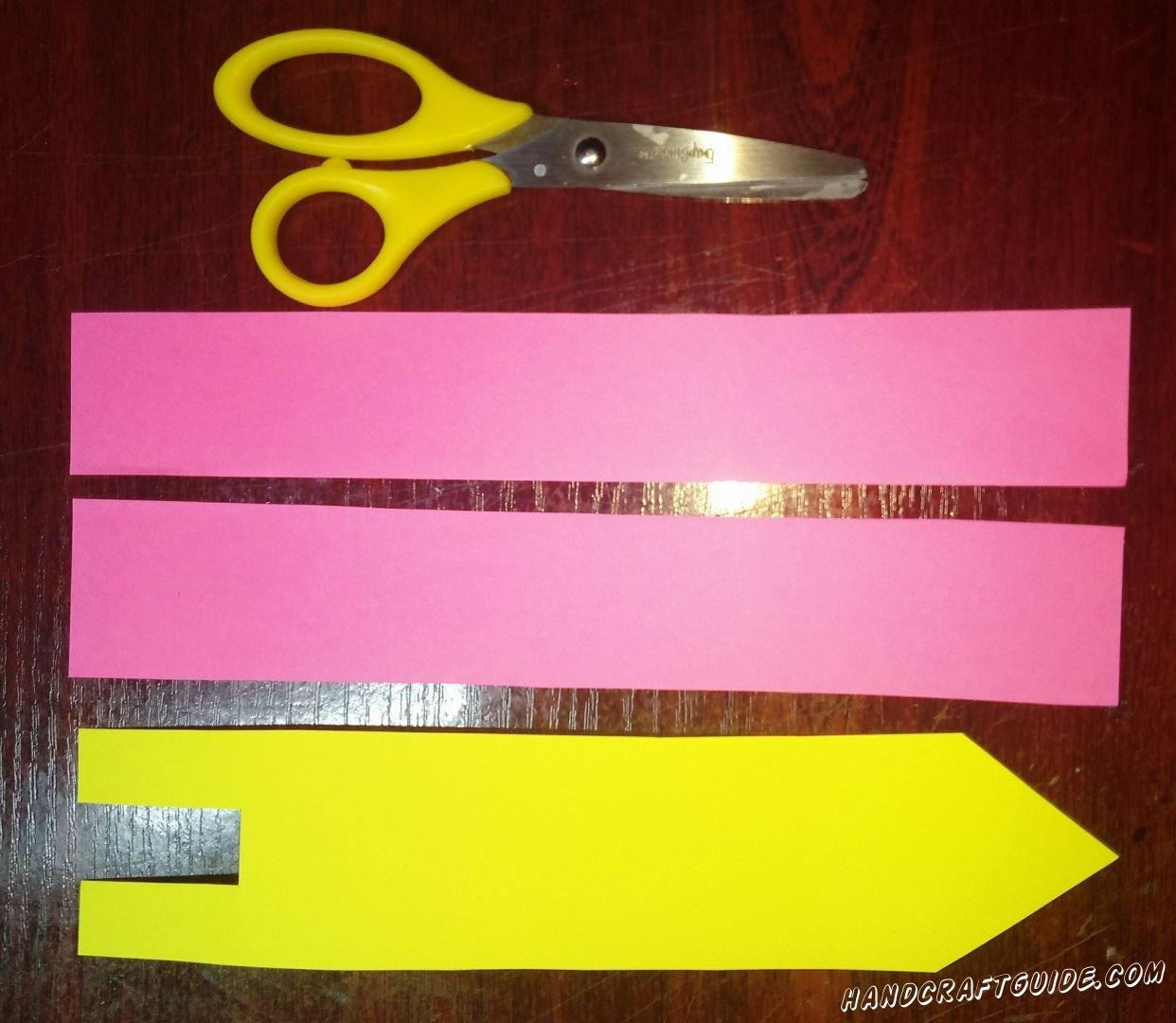 Для начала, вырежем две одинаковые большие полоски из бумаги розового цвета и полоску жёлтого цвета, на которой делаем острый угол на одном краю и прямоугольный вырез на другом конце, как показано на фото.