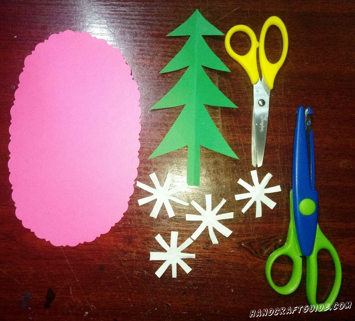 Вырезаем большой розовый овал из бумаги, и красиво делаем узоры по ободку. Также вырезаем зелёную ёлочку и четыре белых снежинки из бумаги.