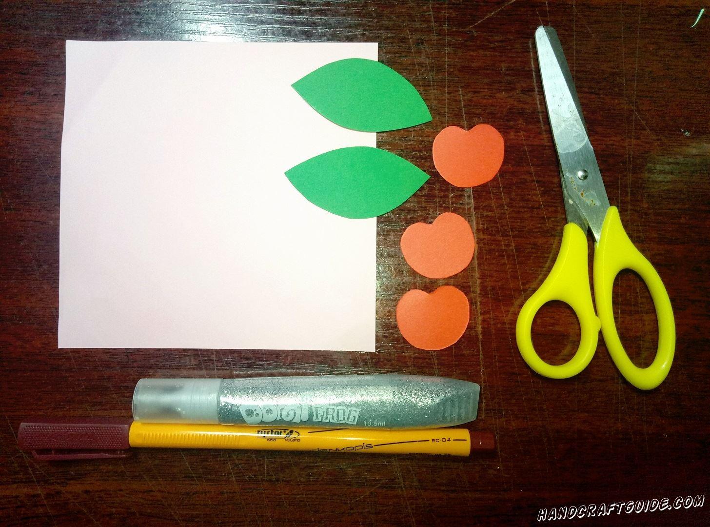 Вырезаем три бумажные красные вишенки и два зелёных листочка