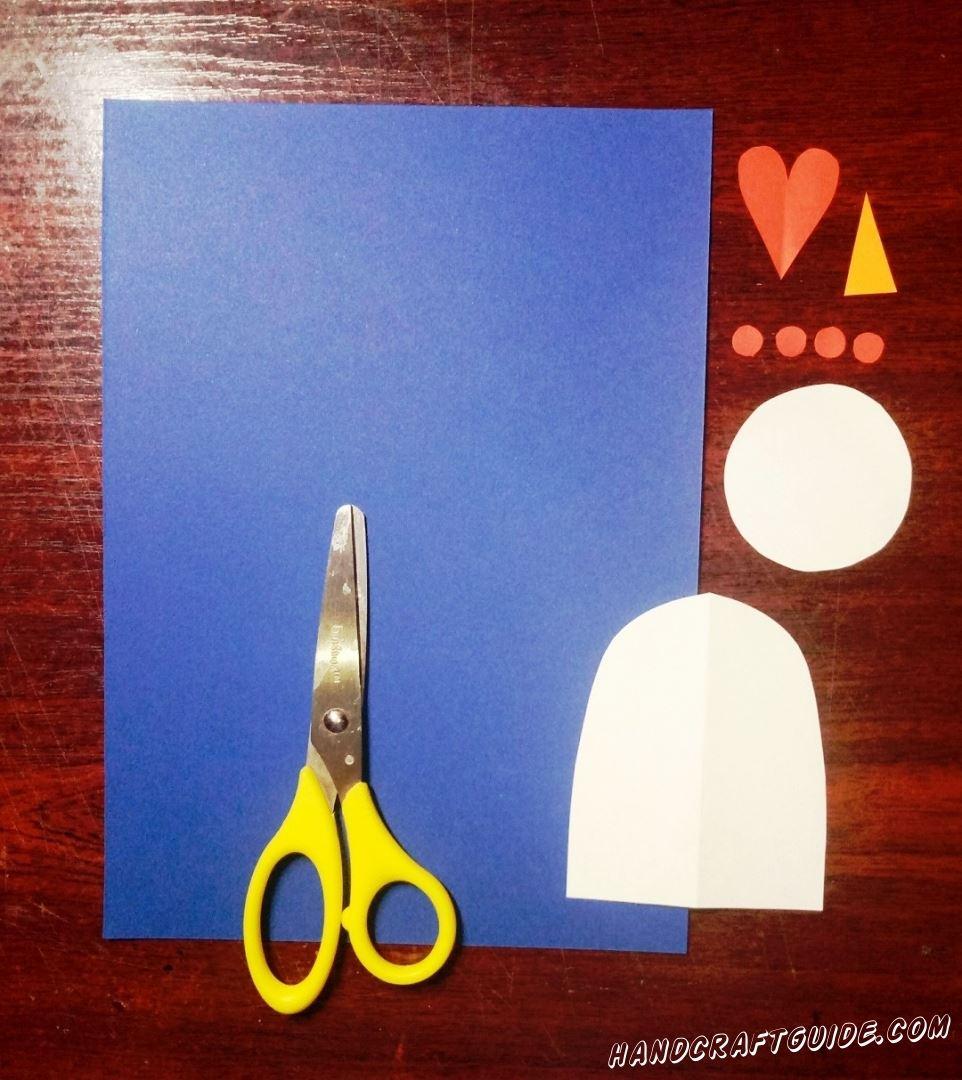 Вырезаем все необходимые бумажные фигурки: тельце и голову снеговика белого цвета, сердечко и четыре пуговки из красной бумаги, а также треугольный оранжевый носик.