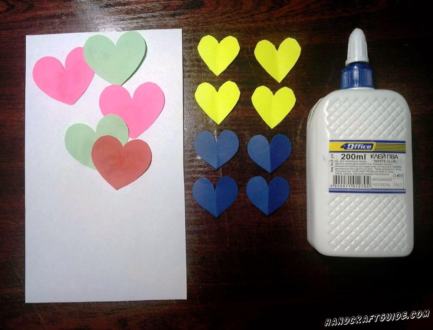 Наклеиваем наши сердечки, на верхней части белого листа бумаги.