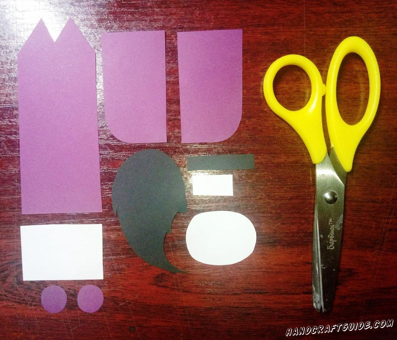 Вырезаем все необходимые нам фигурки из бумаги: широкую фиолетовую полоску с двумя острыми углами на одной стороне, два прямоугольника с одним закругленным углом и два маленьких кружочка. Также нам нужна причёска и тонкая полоска из чёрной бумаги, большой и маленький прямоугольник и овал белого цвета, как показано на фото.