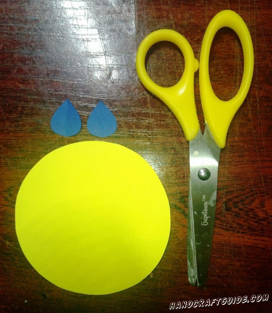 Вырезаем большой бумажный круг желтого цвета и две капельки из голубой бумаги