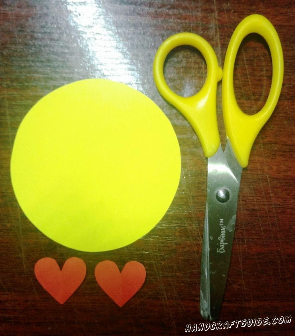 Вырежем желтый круг и два маленьких красных сердечка, из бумаги.