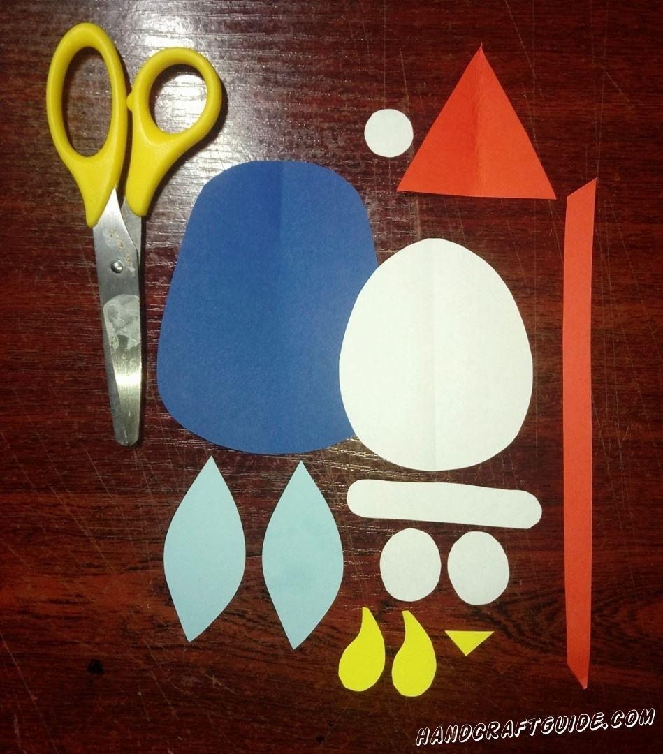Для начала, вырезаем все необходимые нам фигурки из бумаги: большой овал, два маленьких овала, маленький кружочек и полоска на шапочку белого цвета. Также нам понадобится треугольник и шнурок для медалей, из бумаги красного цвета, два голубых лепесточка, две жёлтые лапки и клювик. Ну и основную часть из бумаги синего цвета, как показано на фото.