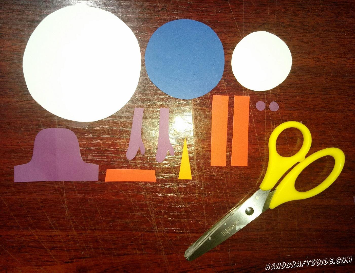 Для начала, нам нужно вырезать из бумаги, все необходимые фигурки: большой и малый круг белого цвета, средний круг синего цвета, фиолетовую шапочку, две ручки и глазки, желтый носик. Осталось только вырезать две одинаковые короткие полоски и бумажную ленточку на шляпу, красного цвета. Теперь смело начинаем склеивать наши фигурки.