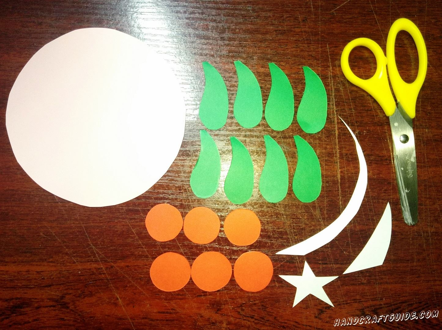 Вырезаем все необходимые бумажные фигурки: большой круг розового цвета, звёздочку и две дуги белого цвета. Также нам нужно вырезать шесть маленьких красных бумажных кружочка и восемь зелёных фигурок в форме капли, как показано на фото.