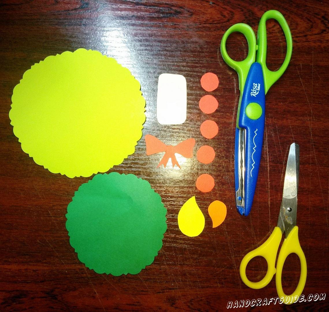 Для начала, нам нужно вырезать из бумаги большой жёлтый круг и чуть меньший зелёного цвета. Круги можно украсить, вырезав узорами по ободку. Также нам понадобится пять маленьких красных кружочка, красный бумажный бантик, маленькая белая свечка из бумаги, и два огонька – оранжевый и, чуть меньшего размера, желтый.