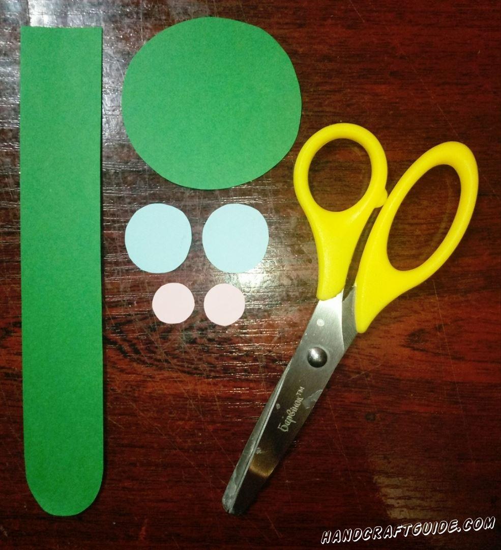 Для начала, вырезаем все необходимые нам бумажные фигурки:  полоску зелёного цвета, с закругленными углами с одной стороны, зелёный круг, два небольших голубых кружка и два светло-розовых ещё меньшего размера.