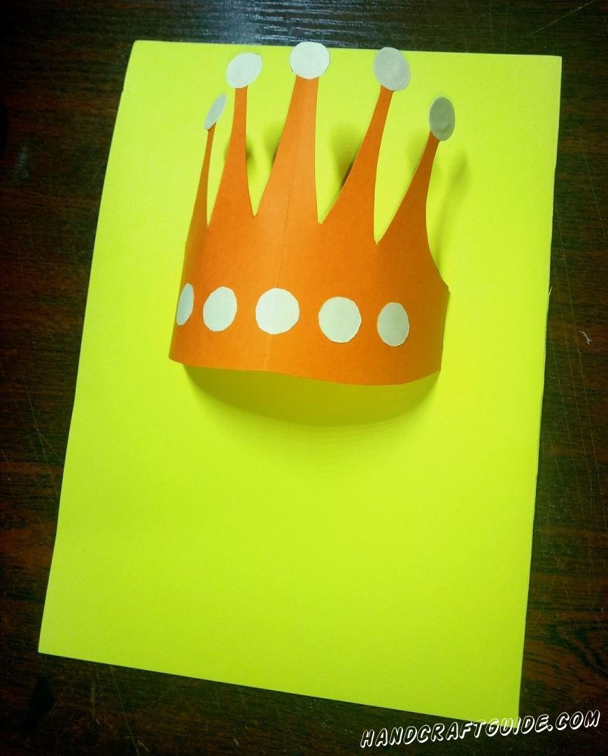 Вставляем края короны в надрезы желтой бумаги