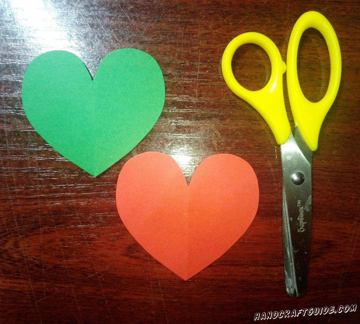 Вырезаем сердечко из бумаги красного цвета и такое же, но чуть большего размера, зелёного цвета.