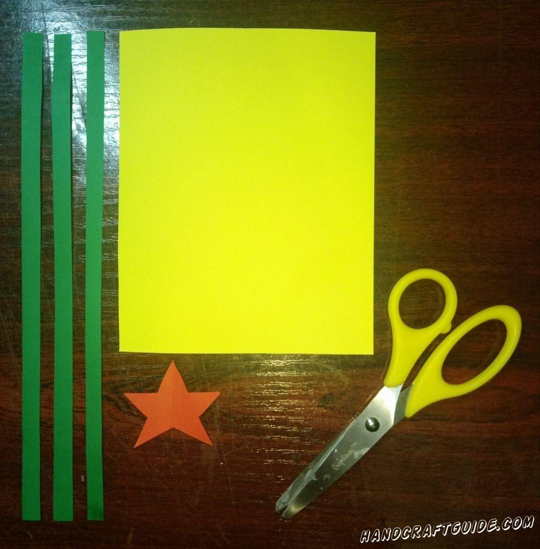 Нам понадобится лист бумаги желтого цвета, красная звёздочка и три одинаковые зелёные полосочки