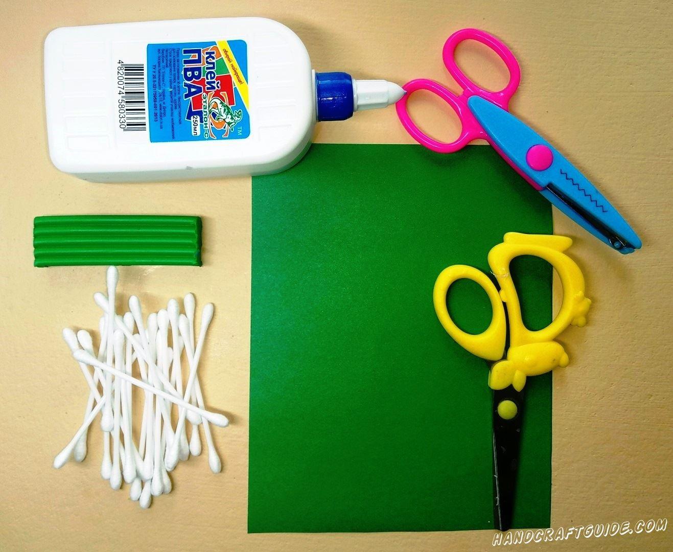 Берем лист зелёной бумаги и разрезаем его чуть выше середины, а также разрезаем ватные палочки пополам