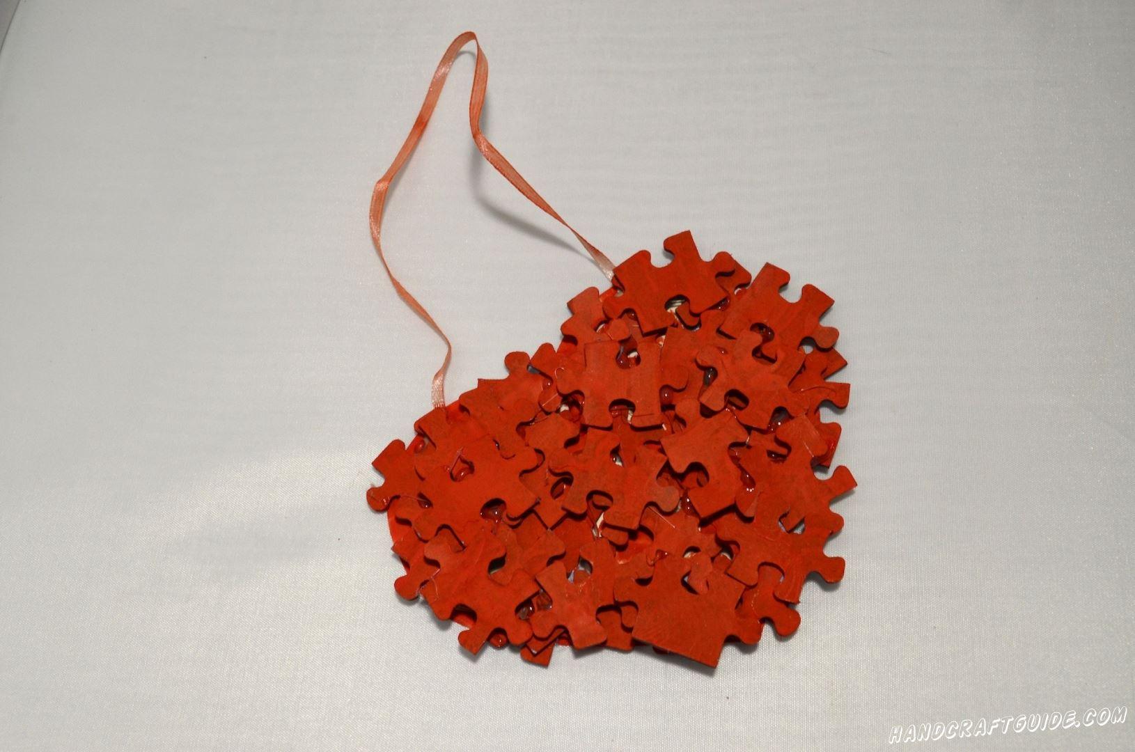 Перед созданием сердца, нужно прицепить ленточку. Берем два пазла, мажем обратную от красного цвета сторону клеем. Ложим на картон одну, затем вторую сторону ленточки и прижимаем их нашими пазлами.