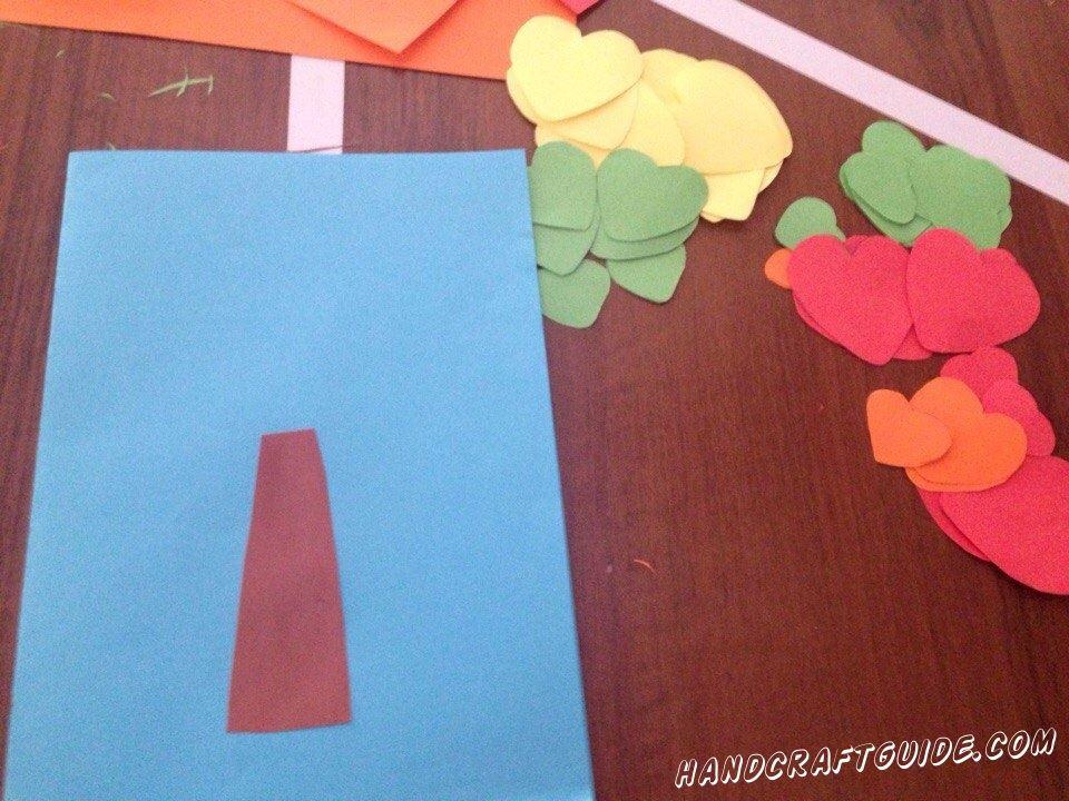 Затем вырезаем небольшой прямоугольник коричневого цвета, который сужается в одной стороне, и приклеиваем его на синий лист бумаги, который послужит нам фоном.